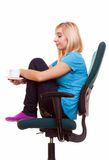 La ragazza premurosa che si rilassa nella sedia tiene una tazza della t Immagine Stock Libera da Diritti