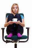 La ragazza premurosa che si rilassa nella sedia tiene una tazza di tè o di caffè. Fotografie Stock Libere da Diritti