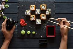 La ragazza prende i bastoncini dei sushi Immagini Stock