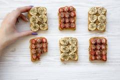 La ragazza prende il pane tostato del vegano con i frutti, semi, burro di arachidi sopra fondo di legno bianco, vista superiore C fotografia stock