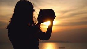 La ragazza prende il selfie sulla macchina fotografica del telefono cellulare sulla bella vista del mare sui precedenti con le lu video d archivio