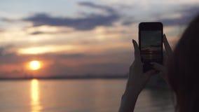 La ragazza prende le foto del tramonto sulla macchina fotografica del telefono cellulare video d archivio