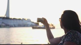 La ragazza prende le immagini sul telefono di una città con acqua nei raggi del tramonto HD, 1920x1080 Movimento lento archivi video