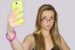 La ragazza prende un autoritratto con il suo Smart Phone Fotografie Stock Libere da Diritti