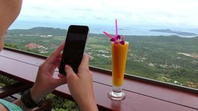 La ragazza prende un'immagine del frullato fresco del mango sui precedenti della vista delle colline verdi archivi video