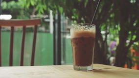 la ragazza prende un vetro di caffè ghiacciato Fotografia Stock