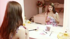 La ragazza prende una collana della perla Sta sedendosi vicino ad uno specchio interno di lusso elegante stock footage