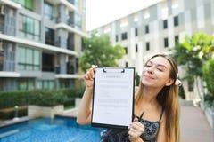 La ragazza propone di firmare il contratto per vivere in paesi caldi b Fotografia Stock