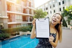 La ragazza propone di firmare il contratto per vivere in paesi che caldi la bella ragazza su fondo dello stagno suggerisce di fir Immagini Stock Libere da Diritti