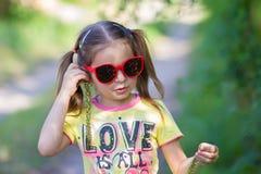 La ragazza prova sopra su se stessa gli orecchini da un albero Fotografie Stock