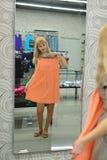 La ragazza prova sopra un nuovo vestito nella parte anteriore del negozio di uno specchio Immagini Stock Libere da Diritti