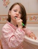 La ragazza pulisce i denti Immagine Stock