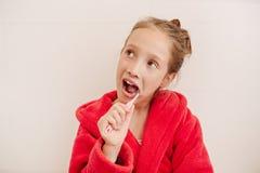 La ragazza pulisce i denti in un bagno Immagini Stock