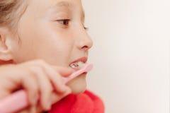 La ragazza pulisce i denti in un bagno Immagine Stock Libera da Diritti