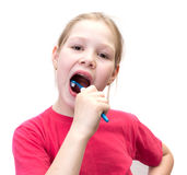 La ragazza pulisce i denti una spazzola Fotografia Stock