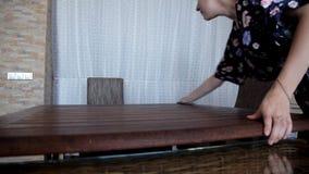 La ragazza pulisce nella cucina di mattina pulisce la tavola dopo la prima colazione video d archivio