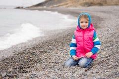 La ragazza quinquennale si siede su un Pebble Beach in vestiti luminosi caldi un giorno nuvoloso con gli sguardi di un sorriso ne Fotografia Stock
