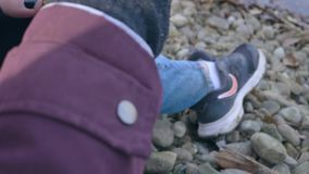 La ragazza raccoglie le foglie sulla sponda del fiume archivi video