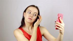 La ragazza raddrizza i suoi capelli ed esamina il telefono stock footage