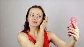La ragazza raddrizza i suoi capelli ed esamina il telefono video d archivio