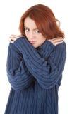 La ragazza Red-haired sta provando a mantenere caldo Immagini Stock