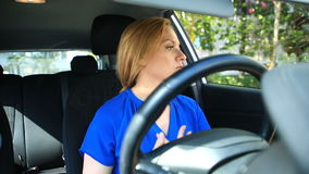La ragazza regola il trucco e l'acconciatura mentre si siede alla ruota dell'automobile stock footage