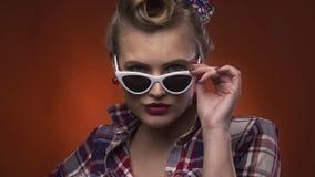 La ragazza retro 50s sta abbassando i suoi vetri con il sorriso sul suo fronte, movimento lento stock footage