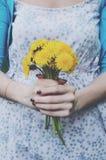 La ragazza in retro vestito da stile che tiene il mazzo di dente di leone fiorisce fotografia stock