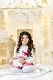 La ragazza riccia adorabile elegante vestita con delizia ammira le luci delle ghirlande di Natale dell'oro e le decorazioni magic Immagine Stock