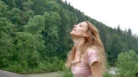 La ragazza riccia felice nelle montagne gode della pioggia dell'estate senza un ombrello La ragazza è felice e risate allegrament video d archivio
