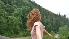 La ragazza riccia felice nelle montagne gode della pioggia dell'estate senza un ombrello La ragazza è felice e risate allegrament archivi video