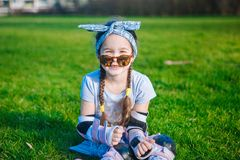 La ragazza riccia sveglia senza dente di latte gode di di sedersi sull'erba in pattini di rullo ed occhiali da sole fotografie stock libere da diritti