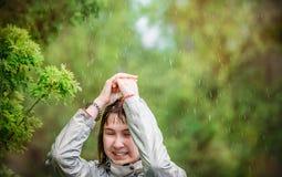 La ragazza riguarda la sua testa di sue mani dalla pioggia Fotografie Stock