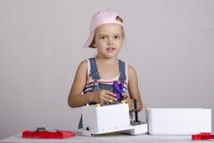 La ragazza ripara i piccoli elettrodomestici del giocattolo Fotografia Stock