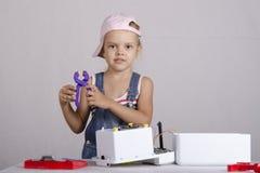 La ragazza ripara i piccoli elettrodomestici del giocattolo Immagini Stock