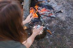 La ragazza riscalda le sue mani sopra il bollitore dal fuoco fotografia stock libera da diritti