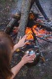 La ragazza riscalda le sue mani sopra il bollitore dal fuoco fotografia stock
