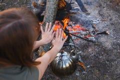 La ragazza riscalda le sue mani sopra il bollitore dal fuoco immagini stock libere da diritti