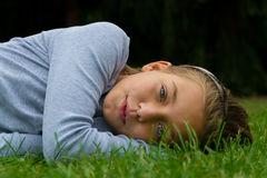 La ragazza risiede da parte in erba che sorride con la bocca aperta Fotografia Stock Libera da Diritti