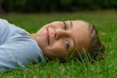 La ragazza risiede nel sorridere dell'erba Fotografia Stock