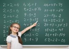 La ragazza risolve il per la matematica sul consiglio scolastico immagine stock