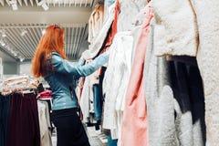La ragazza rossa dei capelli in bomber blu sceglie una pelliccia sulla vendita immagini stock libere da diritti