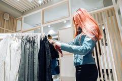 La ragazza rossa dei capelli in un bomber blu sceglie i pantaloni da vendere fotografia stock libera da diritti