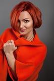 La ragazza rossa in un rivestimento rosso ad una parete Fotografia Stock Libera da Diritti