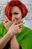 La ragazza rossa in un rivestimento verde ad un mattone della parete Fotografie Stock