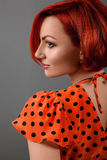 La ragazza rossa in un vestito rosso ad una parete Fotografia Stock Libera da Diritti