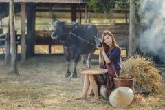 La ragazza rurale asiatica ascolta la radio sul fondo dell'azienda agricola Immagini Stock Libere da Diritti