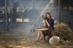 La ragazza rurale asiatica ascolta la radio sul fondo dell'azienda agricola Immagine Stock
