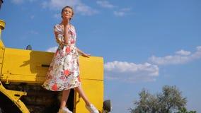 La ragazza rurale in vestito dà il bacio dell'aria sul cofano della mietitrebbiatrice sul fondo del cielo stock footage