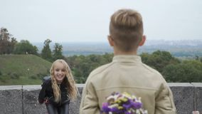 La ragazza salta dalla gioia, tenute del ragazzino un mazzo dei fiori dietro la parte posteriore stock footage